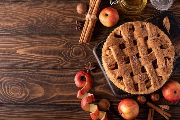 木製のテーブルにシナモンと蜂蜜と秋のリンゴからアップルパイ