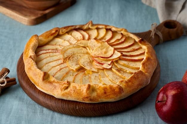Яблочный пирог, галет с фруктами, сладкая выпечка на синей скатерти, сладкая кростата