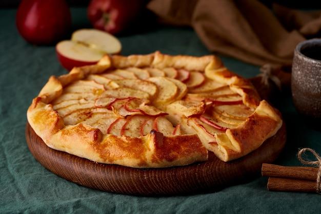 アップルパイ、フルーツのガレット、濃い緑色のテーブルクロスに甘いペストリー、クローズアップ、側面図