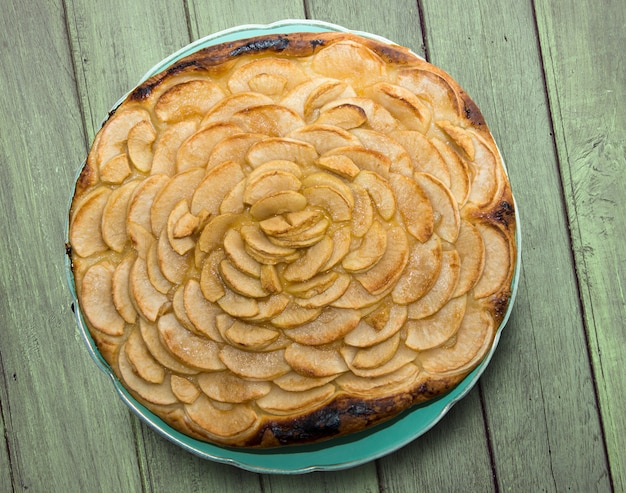 Apple pie on a green wooden table