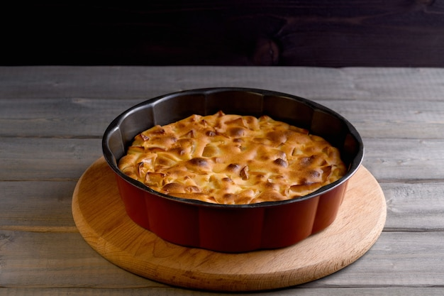 Яблочный пирог круглой формы на деревянном фоне. яблочная шарлотка