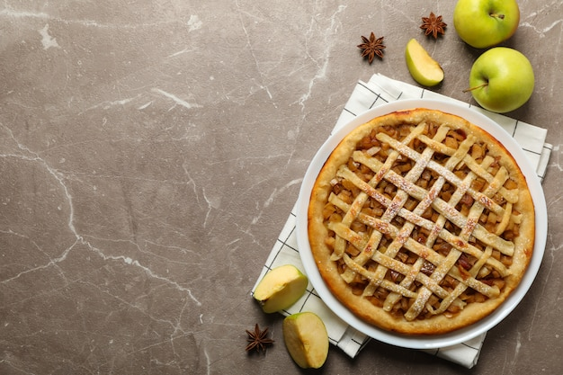 Apple pie and ingredients on gray background