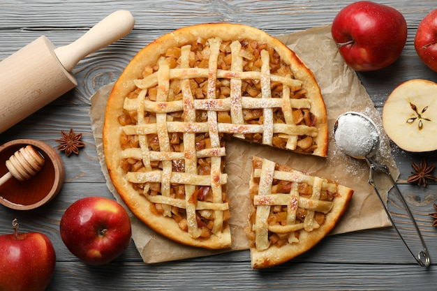 Apple pie and ingredients on wooden background