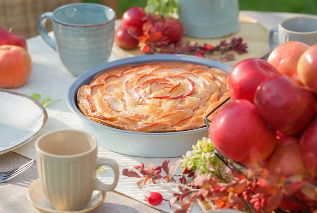 Яблочный пирог на накрытом столе в саду в солнечный день
