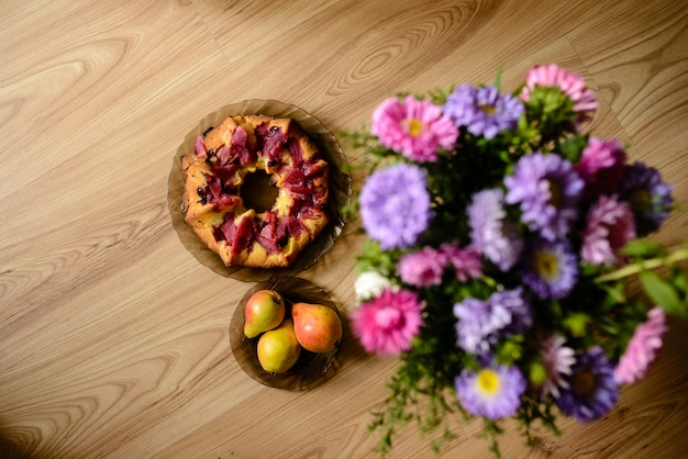 Apple pie, pears and flowers on the table.