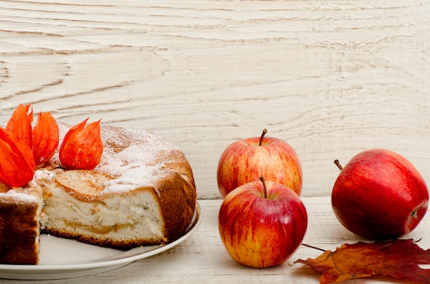 Apple pie and ripe apples on a light wooden table