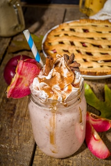 Apple pie smoothie. crazy shake cocktail with traditional autumn apple pecan flavor, wooden dark background copy space