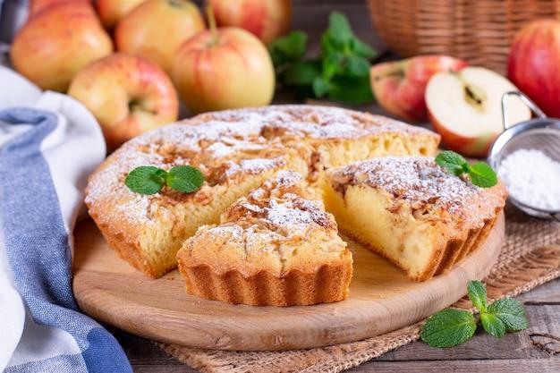 アップルパイ、スポンジケーキ、木製のテーブルにリンゴとシャルロット