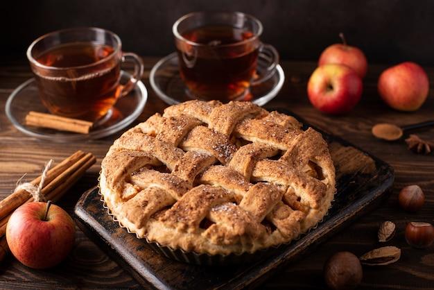木製のテーブルにシナモンと熱い紅茶とアップルパイ