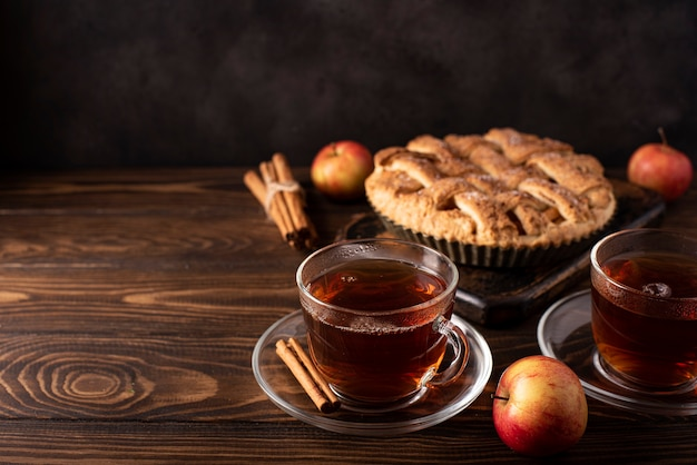 Apple pie with cinnamon and hot black tea on a wooden table