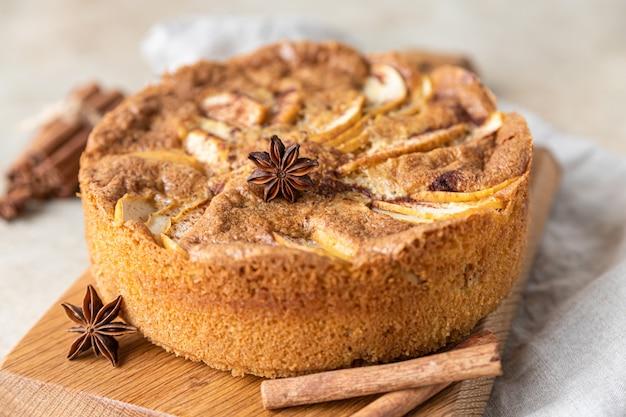 木の板にシナモンを添えたアップルパイリンゴとスパイスを添えたセモリナケーキ