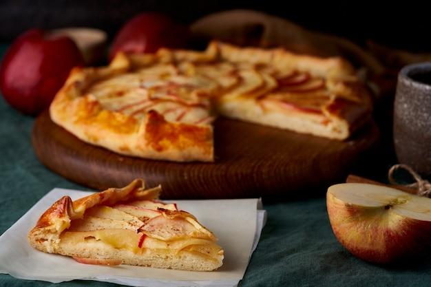 フルーツとガレットのピーススライス、濃い緑色のテーブルクロスにスライスした甘いペストリーとアップルパイ