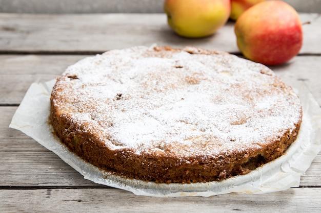 Яблочный пирог с цельнозерновой мукой на деревянном фоне. концепция здорового питания