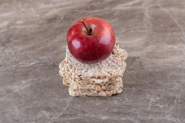 Mela e un mucchio di gallette di riso soffiato sulla superficie di marmo