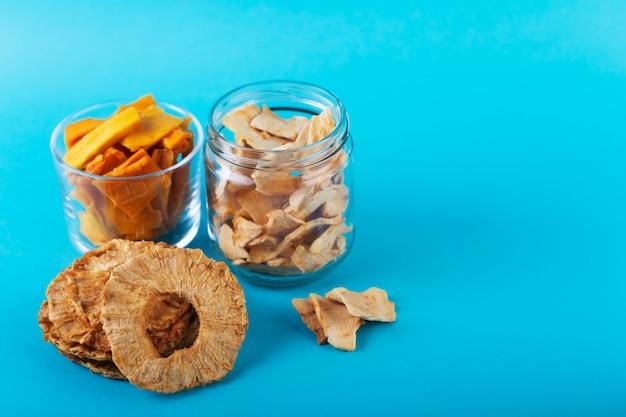 瓶にリンゴ、パイナップル、マンゴーのチップとテーブルの上のこの果物の破片