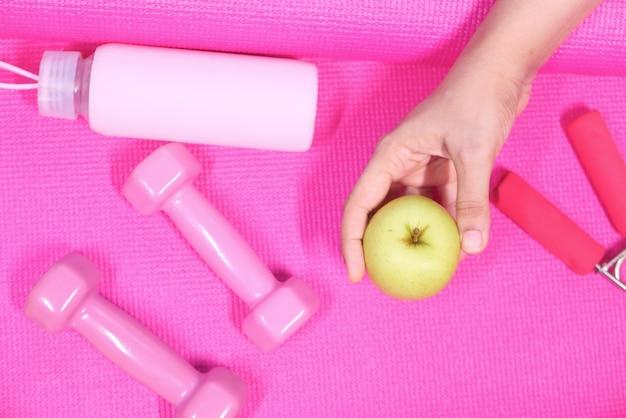 アップル、ピンク色のダンベル、エクササイズマットの水筒。
