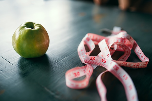 Apple and pink measuring tape on wooden table closeup. weight loss diet concept, fat or calories burning
