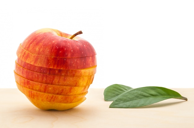 Apple preserved its shape, but cut into slices and two leaves on a wooden table.