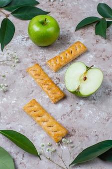 Biscotti della pasta sfoglia di apple in piatto con le mele fresche, vista superiore di forma della mela