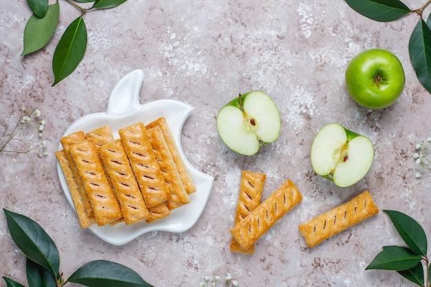 Biscotti di pasta sfoglia di mele in lamiera a forma di mela con mele fresche