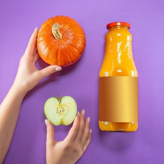 Бутылка яблока, тыквы и сока на фиолетовом