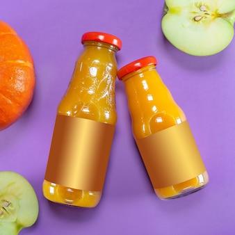 Яблоко, тыква и бутылки сока на фиолетовом