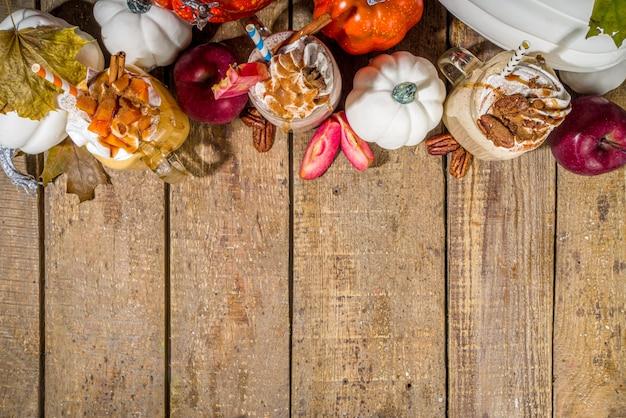 アップル、カボチャ、ピーカンパイのスムージードリンク。暗い木製の背景のコピースペースに、伝統的な秋のベーキングケーキフレーバーカクテルセット