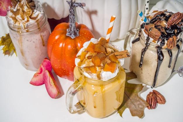 アップル、カボチャ、ピーカンパイのスムージードリンク。白い背景のコピースペースに、伝統的な秋のベーキングケーキフレーバーカクテルセット