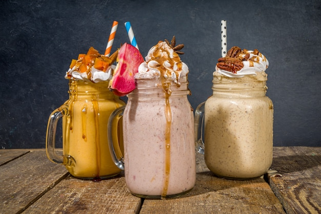 Apple, pumpkin and pecan pie smoothie drinks. traditional autumn baking cake flavor cocktails set, on dark wooden background copy space