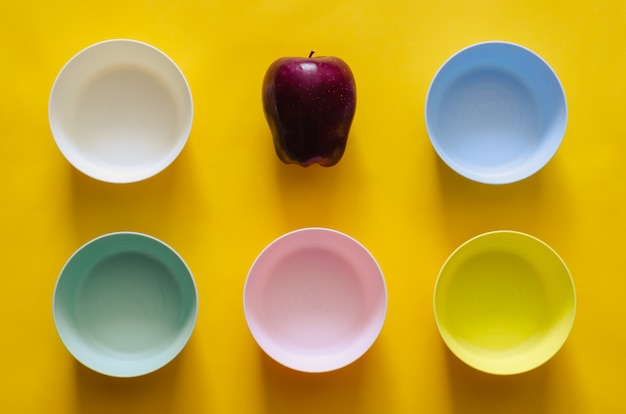 An apple put among the colorful small bowls on yellow background for vegan concept.