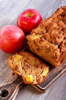 Apple and raisin cake, sliced on board, selective focus