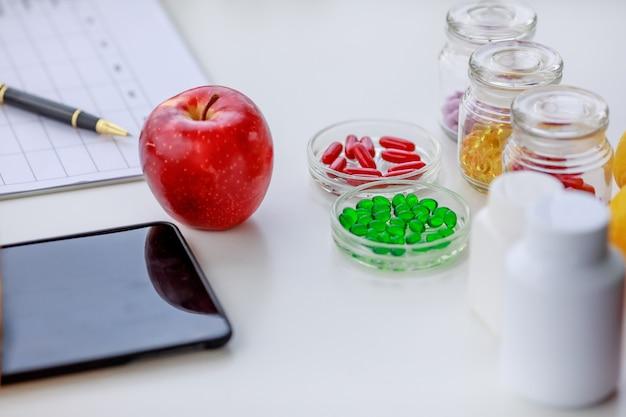 몇 병에 담긴 사과, 빨강, 녹색, 노란색 알약, 휴대전화, 펜은 영양사 테이블에 주간 식사 계획이 있습니다. 영양 테이블 상위 뷰 사진에 대한 개념입니다.
