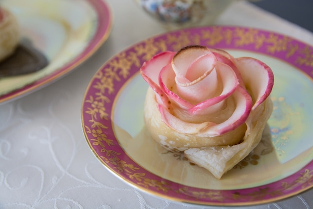 A apple's rose puff pastry dessert on beautiful ware.