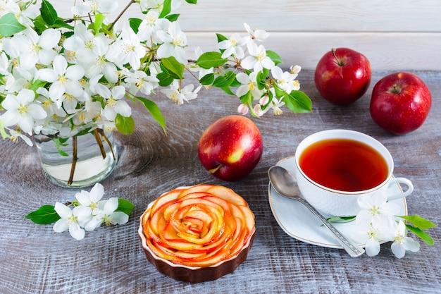 Apple shaped roses pie and cup of tea on wooden table