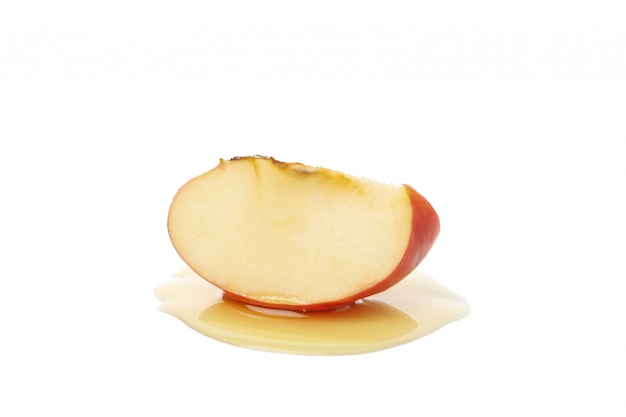 Кусок и мед яблока изолированные на белизне. натуральное лечение