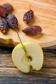 Кусок яблока с датами на разделочной доске и деревянном, взгляде высокого угла.