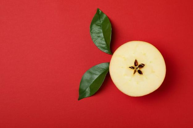 赤の背景に葉を持つリンゴのスライス