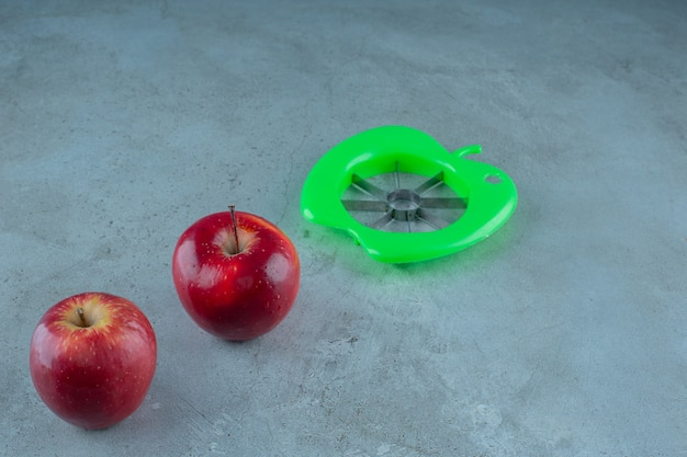 Ломтик для яблок и целые яблоки на мраморном фоне.