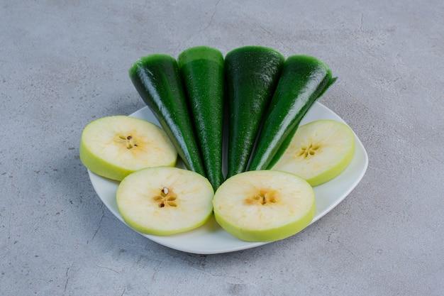 Fette di mela e spuntino aspro al gusto di mela su un piatto su fondo di marmo.