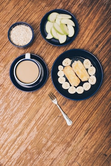 Apple slices; muesli; coffee; banana and toast in the breakfast on wooden backdrop