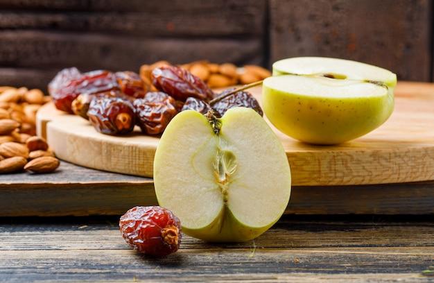 Яблочные ломтики с финиками и миндалем на деревянных и разделочных досках, вид сбоку на каменную плитку и деревянные