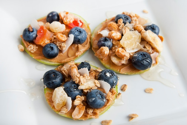 Apple slices with peanut butter and blueberries. health food.