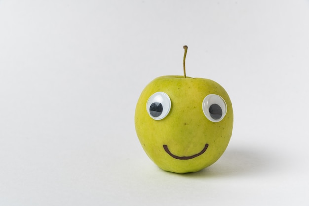 Apple smiley on white background. apple with googly eyes and drawn smile.