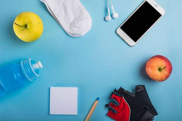 Apple; sock; earphone; water bottle; adhesive note; pencil; glove and cellphone on blue background