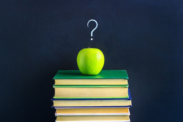 Apple on stack books and question mark.