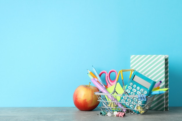 Apple and stationary on grey table. study concept