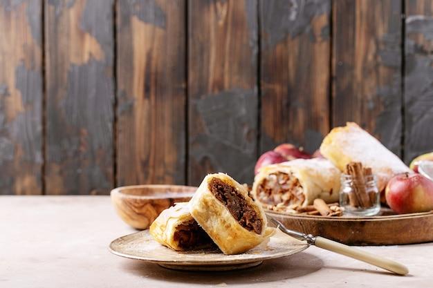 白いテクスチャの背景の上に新鮮なリンゴ、シナモンスティック、クルミを添えたアップルシュトルーデル