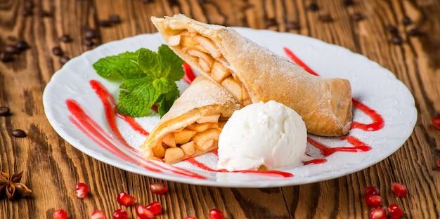 Яблочный штрудель, посыпанный сахарной пудрой и мороженым