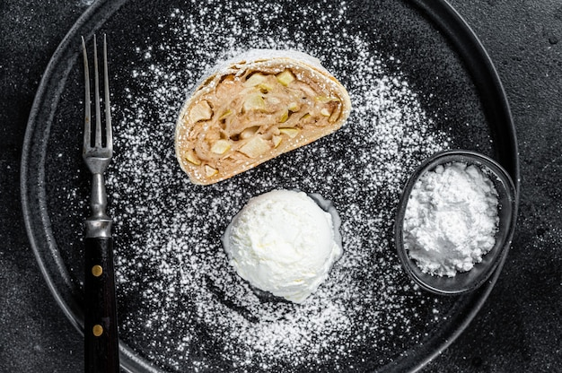 Apple strudel with cinnamon, powdered sugar and vanilla ice cream on a plate. black background. top view.