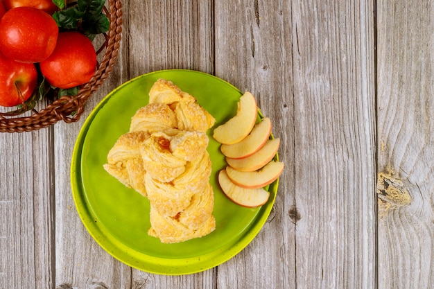 Apple strudel with fresh red apples on wooden table
